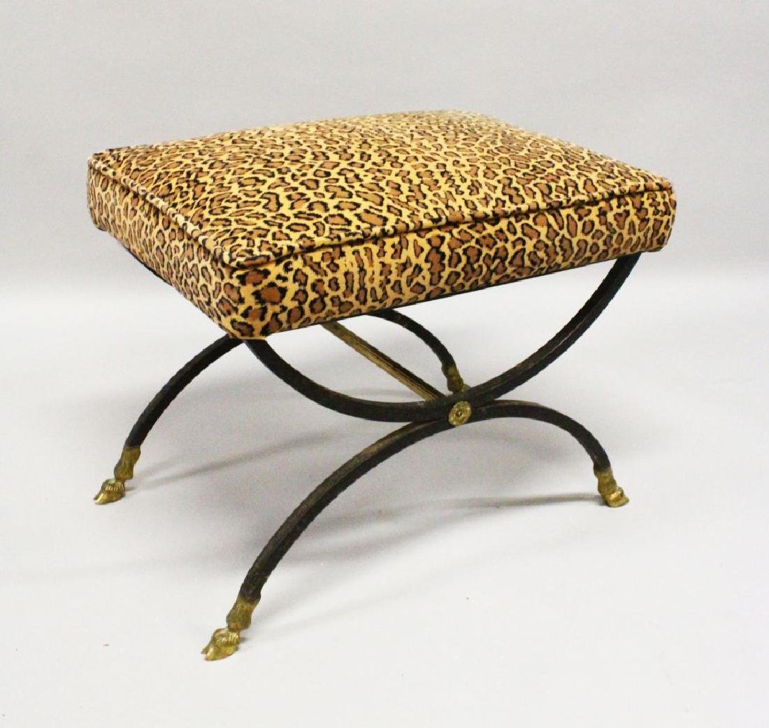 A BRONZE AND IRON CROSS FRAME STOOL with padded top.