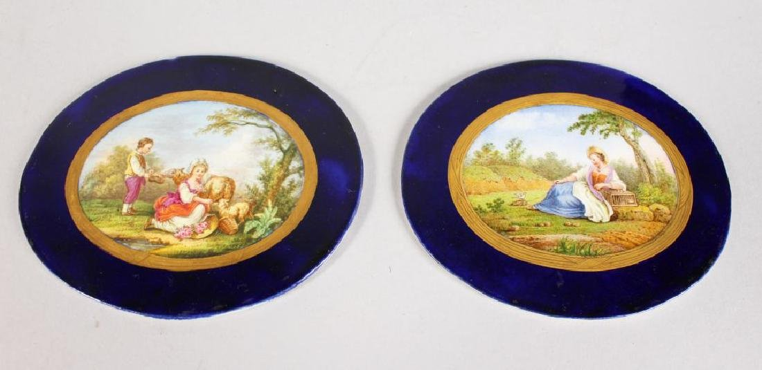 A PAIR OF OVAL PORCELAIN PANELS, rich blue borders, the