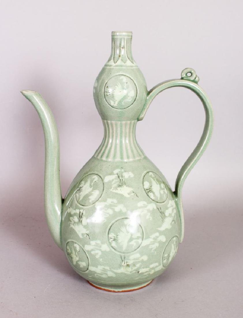 A GREEN EWER decorated with storks in circular panels.