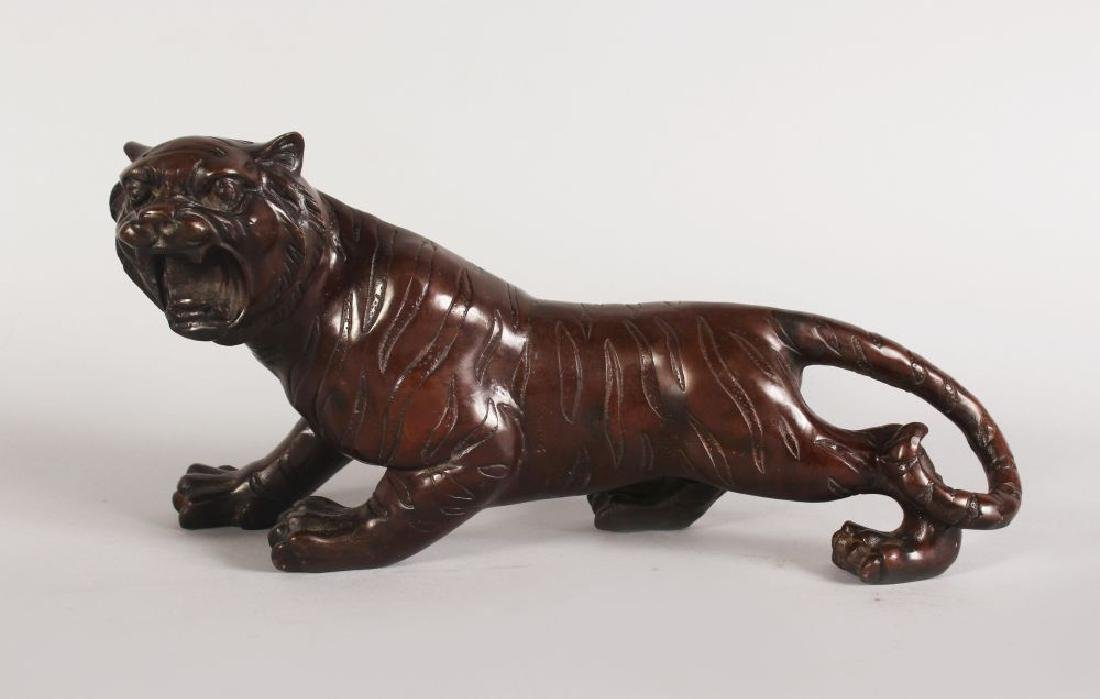A JAPANESE BRONZE MODEL OF A TIGER.  12ins long.