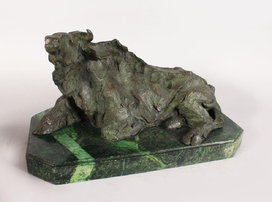 AN UNUSUAL ABSTRACT BRONZE OF A RECUMBENT COW, on a