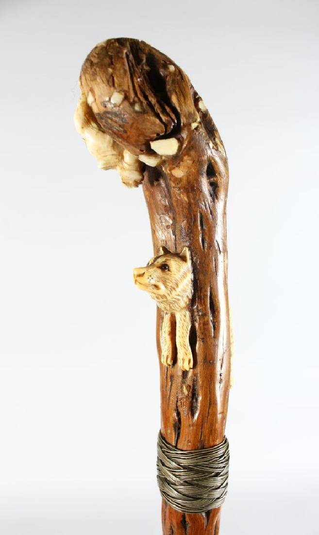A WALKING STICK with carved wooden WOLF AND CAT handle.