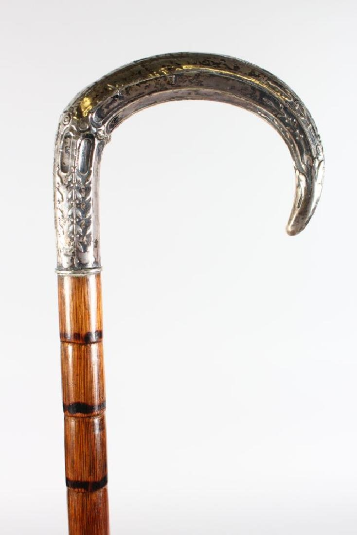 A WALKING STICK with carved SILVER HANDLE.