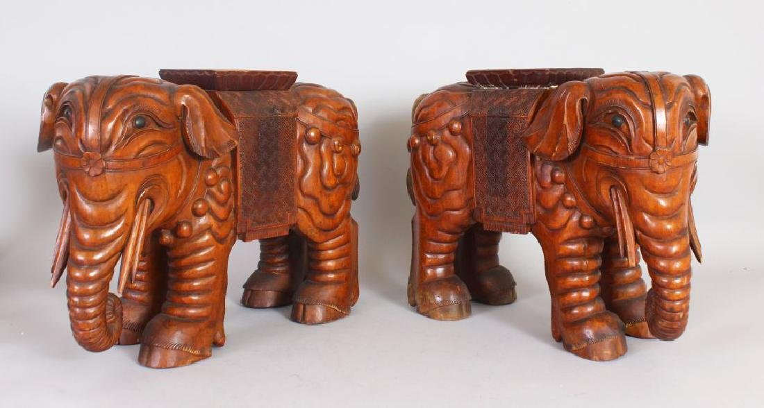 A PAIR OF EASTERN CARVED WOOD ELEPHANT SEATS.  1ft 6ins