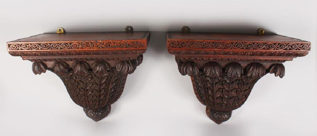 A GOOD PAIR OF CARVED WOOD WALL BRACKETS of ISLAMIC
