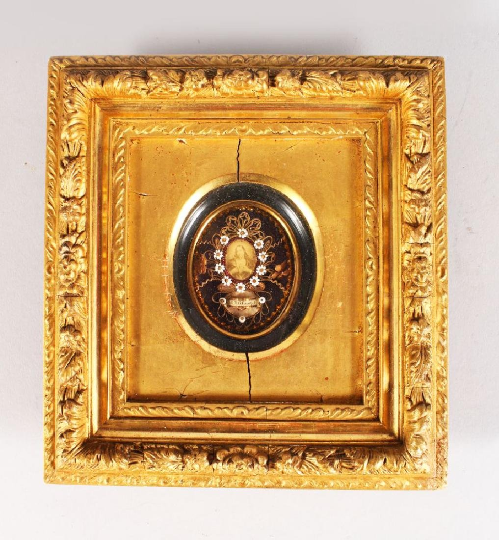 A RELIGIOUS ROLLED PAPER RELIQUARY in a gilt frame.