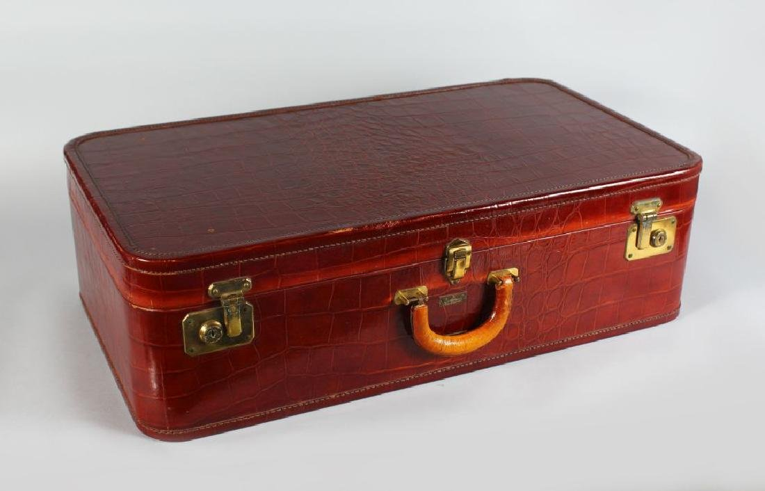 AN EMBOSSED LEATHER SUITCASE, BY CAVANAUGH, complete