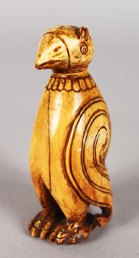 AN EARLY INUIT CARVING OF A PENGUIN, standing upright,