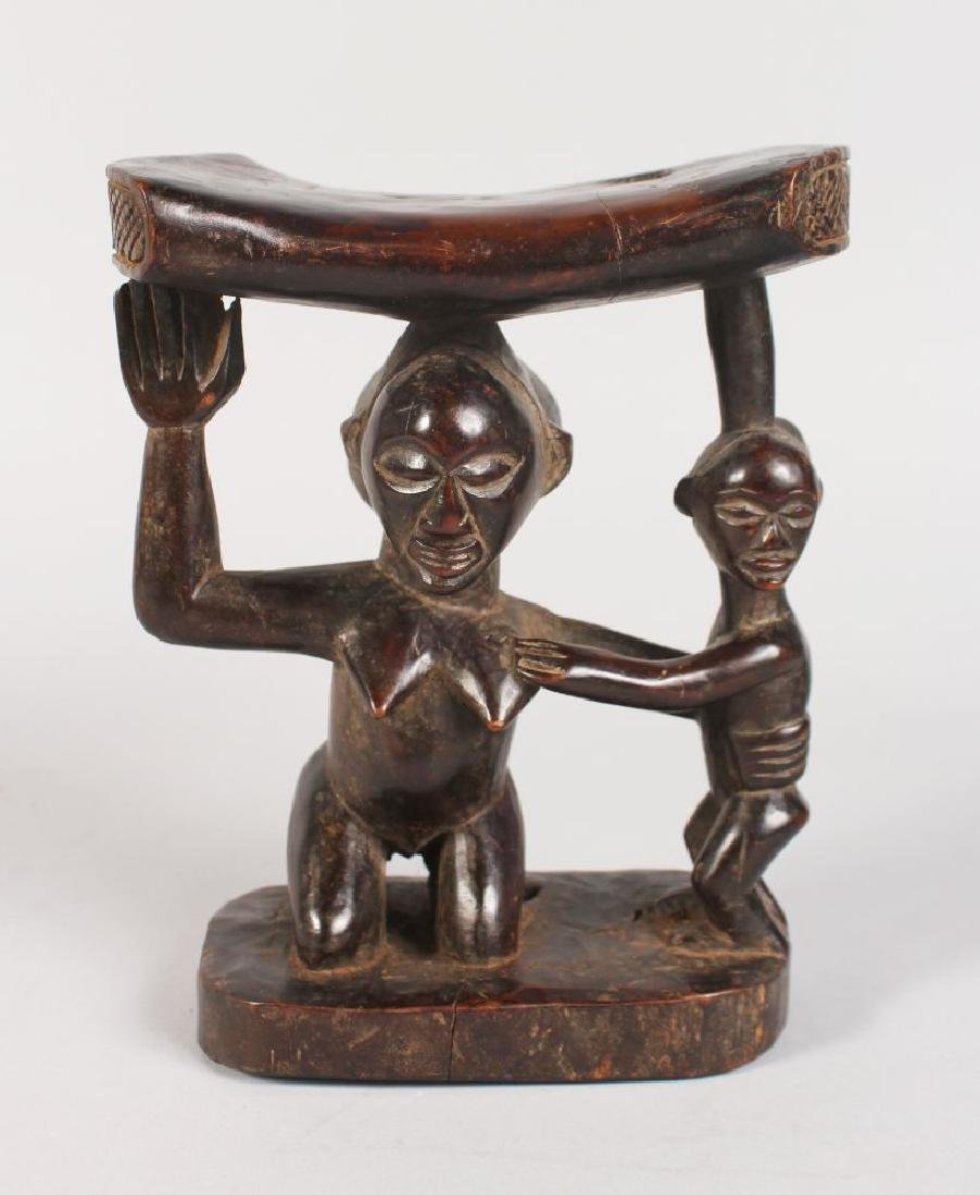 "A CARVED TRIBAL NECK REST, ""MOTHER AND CHILD"".  7ins"