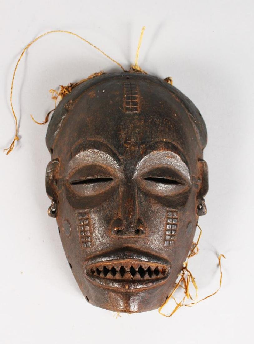 A PAINTED TRIBAL MASK with sharp teeth.