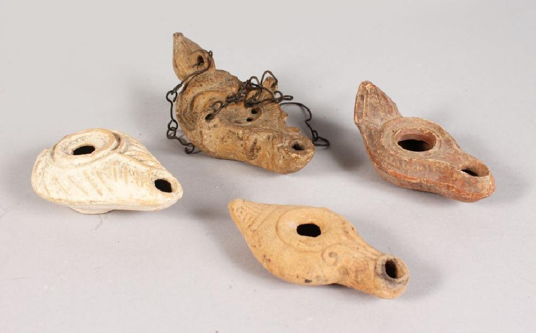 FOUR ROMAN TERRACOTTA OIL LAMPS.