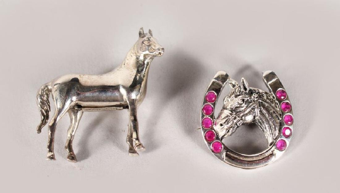 TWO SILVER HORSE BROOCHES.