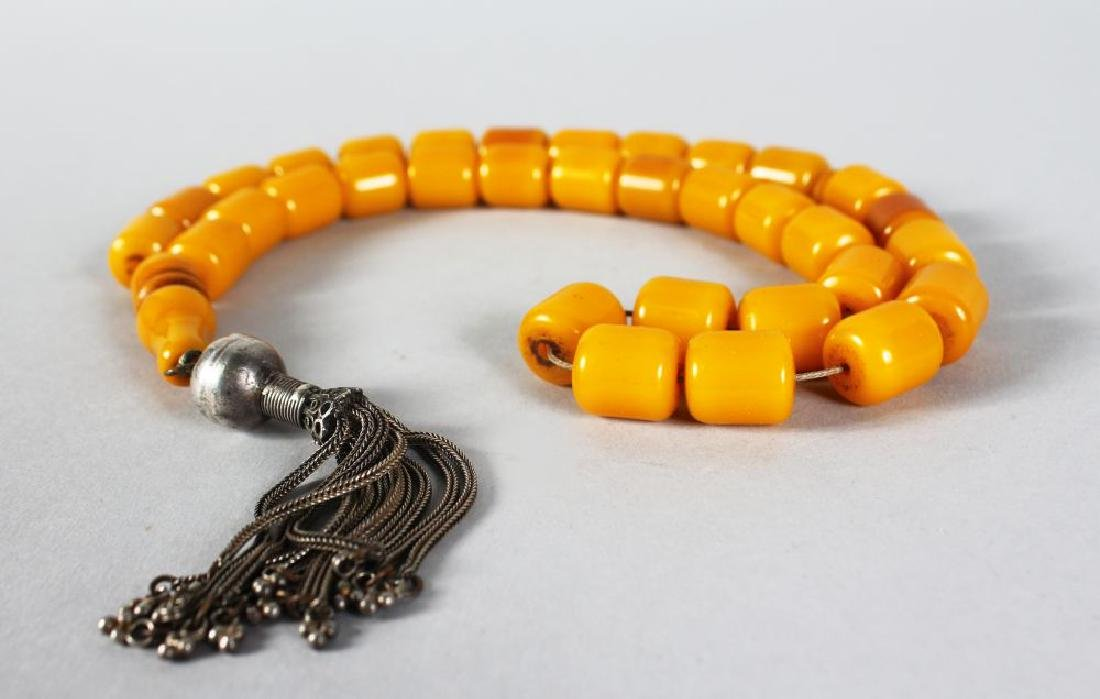 A SUPERB STRING OF AMBER BEADS with silver tassel.