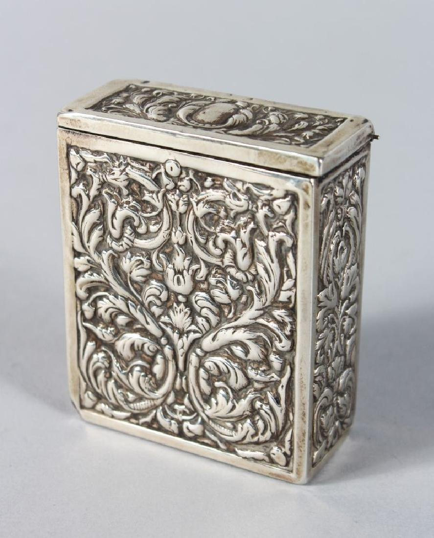 A SILVER BOX AND LID with repousse decoration.