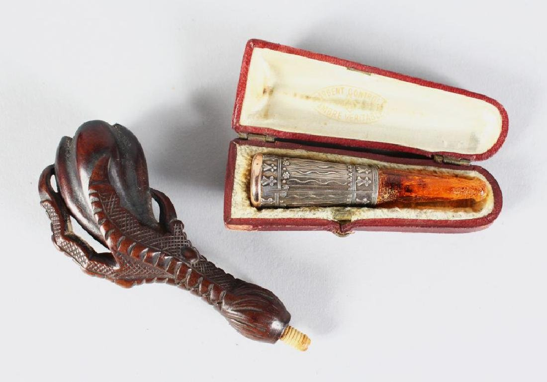 A CIGARETTE HOLDER in leather case and A CLAW PIPE.