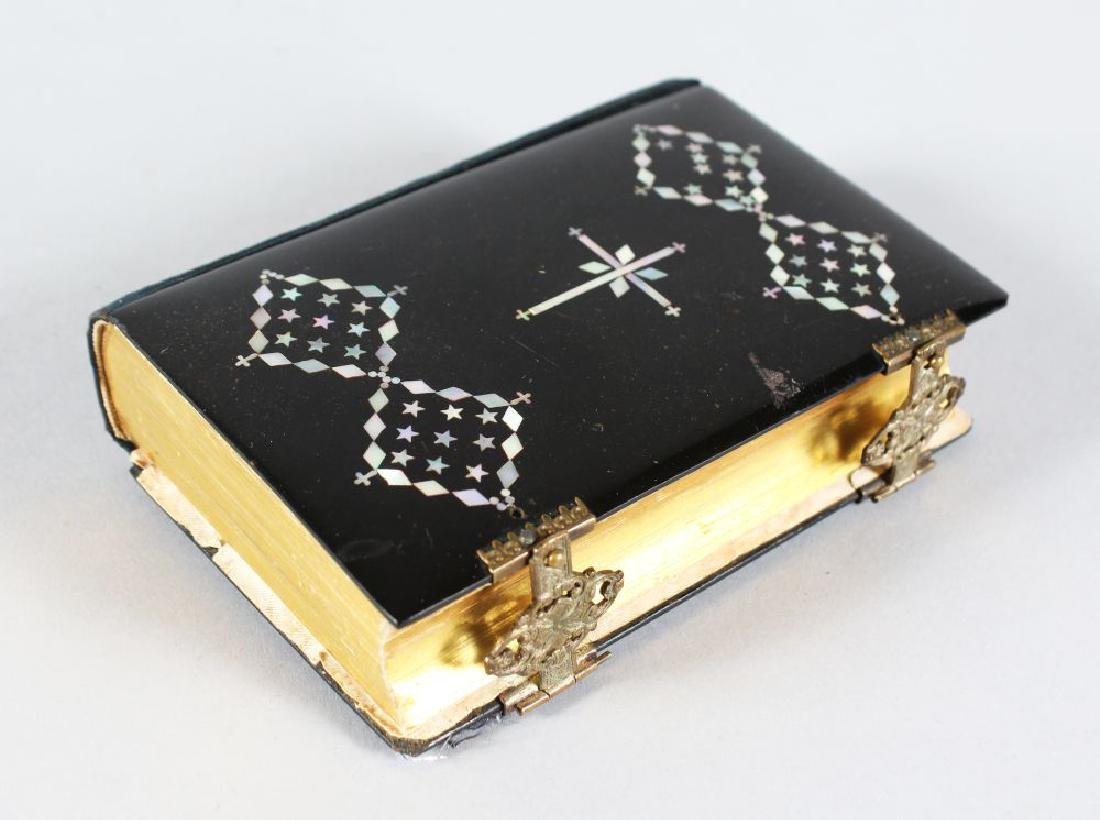 A PRAYER BOOK with mother-of-pearl cross.
