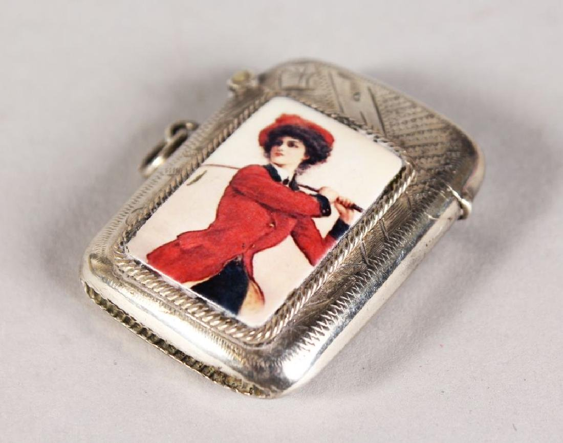 AN ENGRAVED GEORGE V SILVER GOLFING VESTA, a lady with