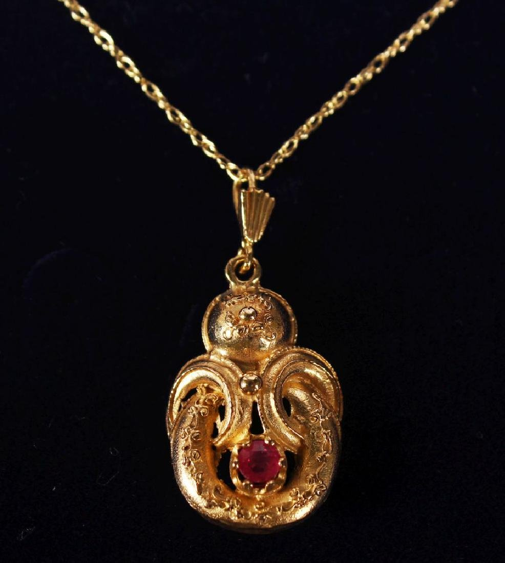 A 9CT GOLD VICTORIAN STYLE RUBY SET PENDANT AND CHAIN.
