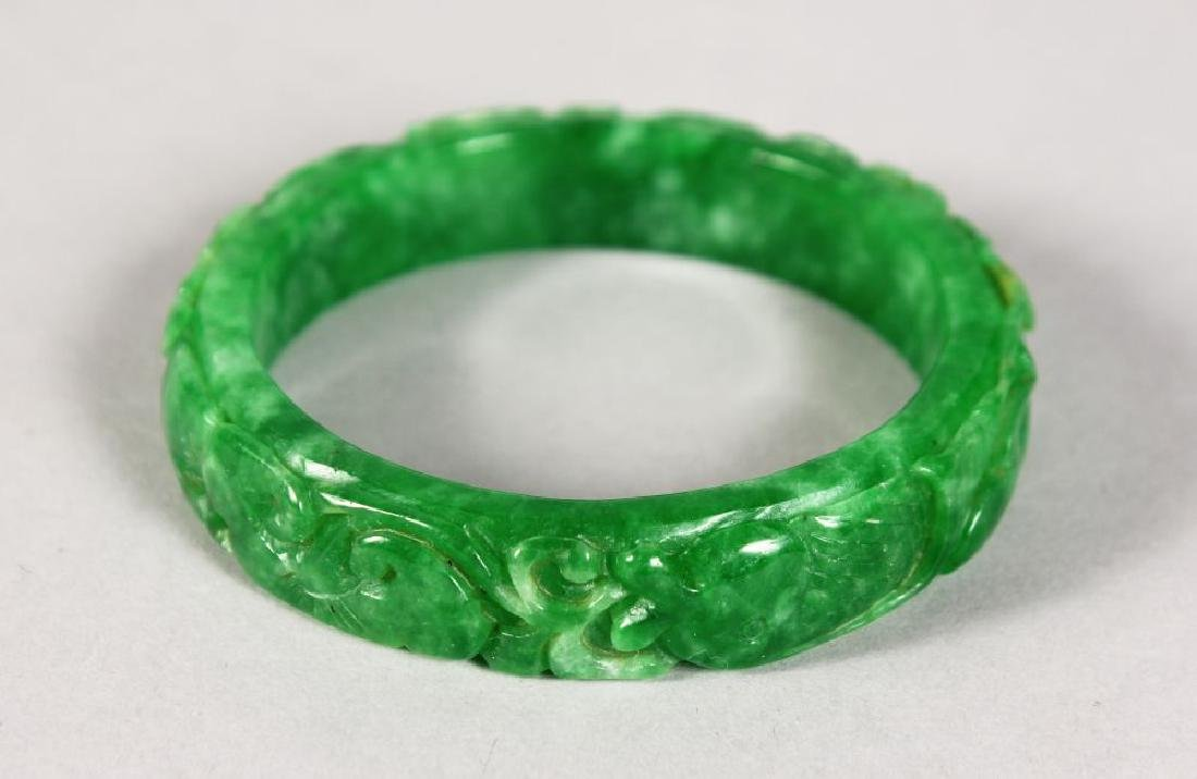 A CARVED APPLE GREEN JADE BANGLE.
