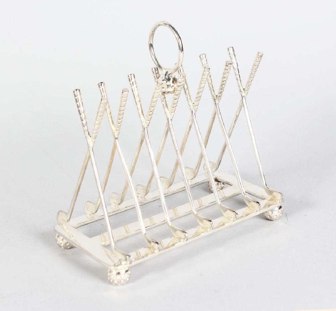 "A PLATED ""GOLF"" TOAST RACK with seven pairs of clubs"