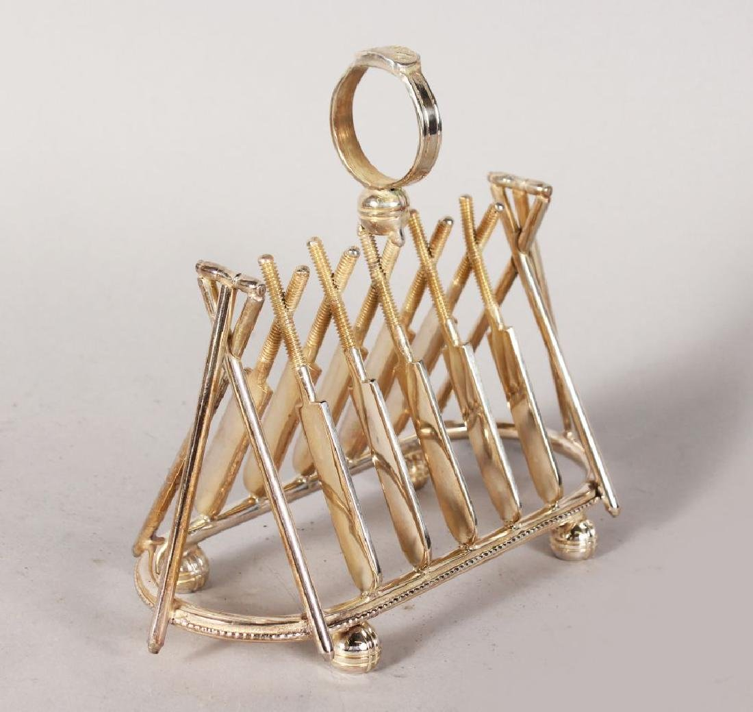 "A PLATED TOAST RACK ""CRICKET"" of five pairs of bats,"