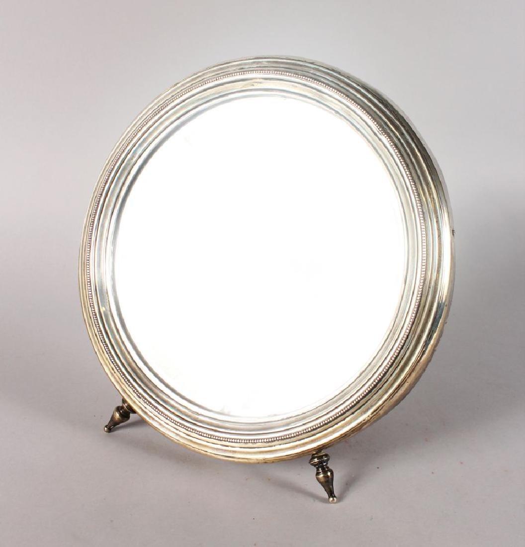 A SILVER CIRCULAR EASEL MIRROR.  12ins diameter.