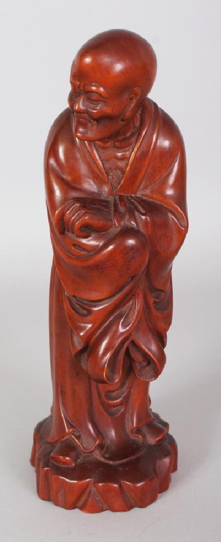 A GOOD QUALITY CHINESE CARVED WOOD FIGURE OF A STANDING