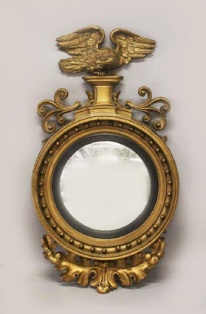 A REGENCY GILTWOOD CONVEX MIRROR, with eagle and