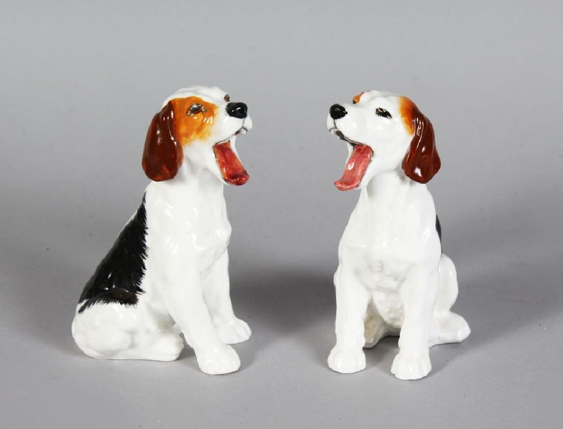 A PAIR OF ROYAL DOULTON PORCELAIN SEATED DOGS, yawning,