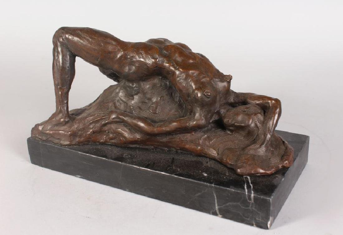 AN ABSTRACT BRONZE FEMALE NUDE, reclining on a rock, on