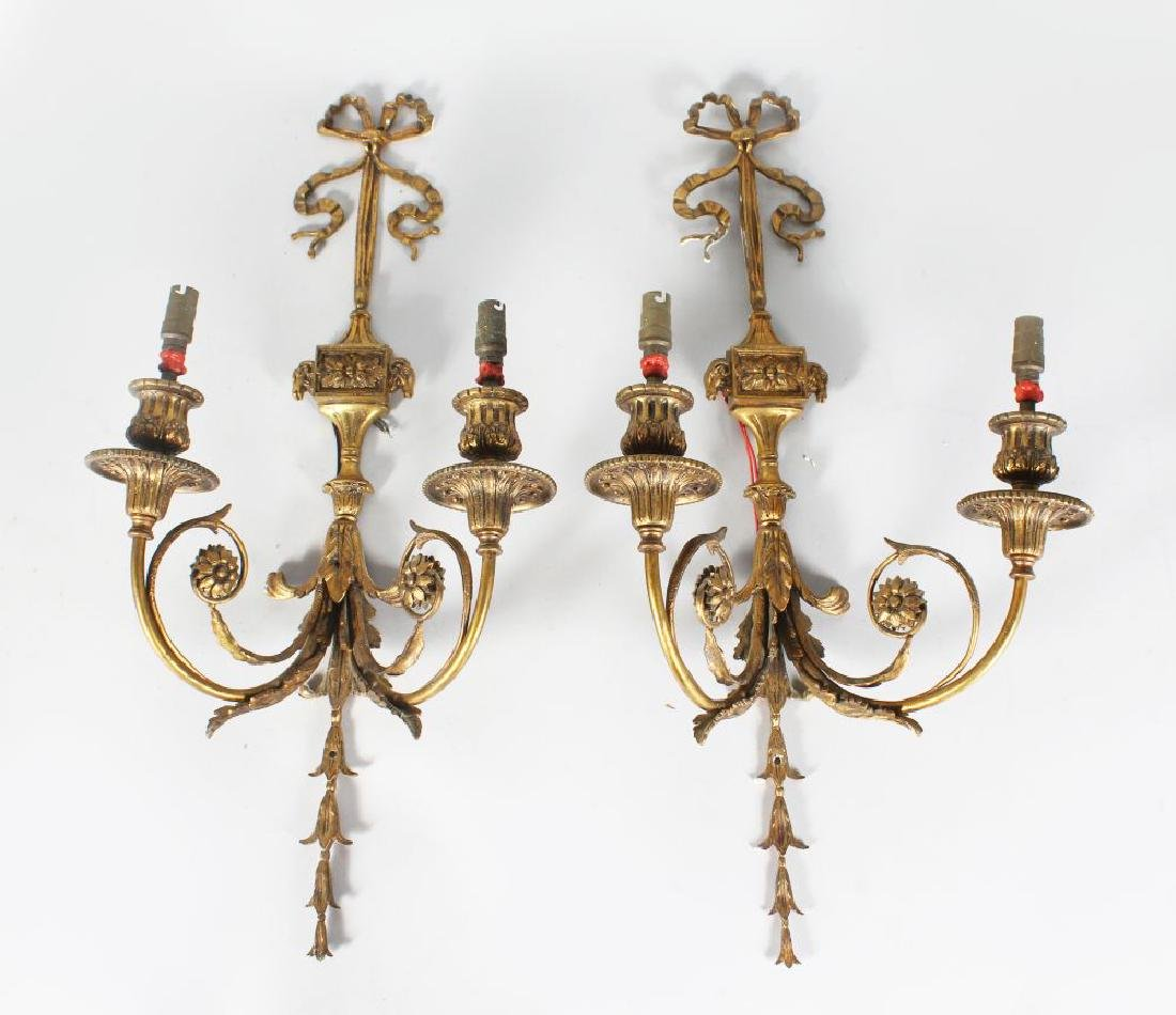 A PAIR OF GILT BRASS WALL SCONCES, with ribbon and bow