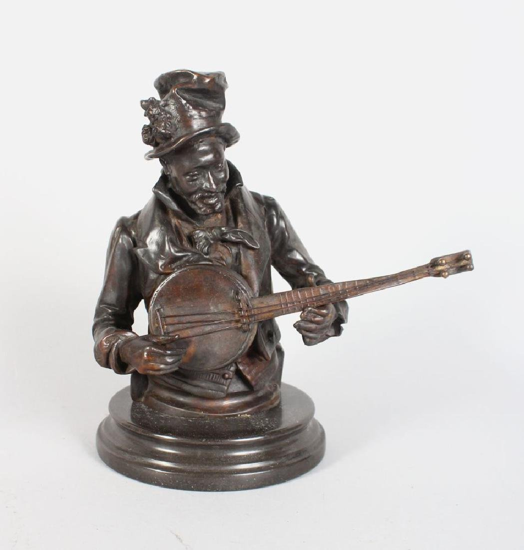 A BRONZE HEAD AND SHOULDERS OF A MAN PLAYING A BANJO,