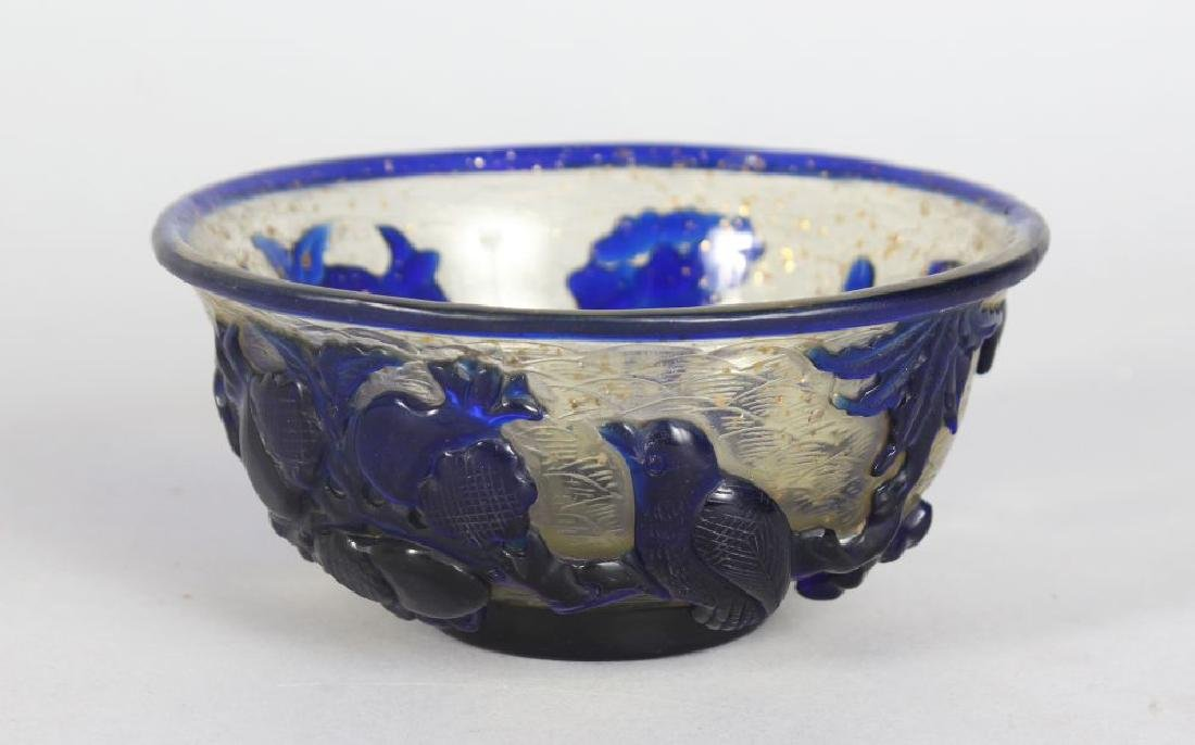 A CHINESE RELIEF CARVED GLASS BOWL.  5ins diameter.