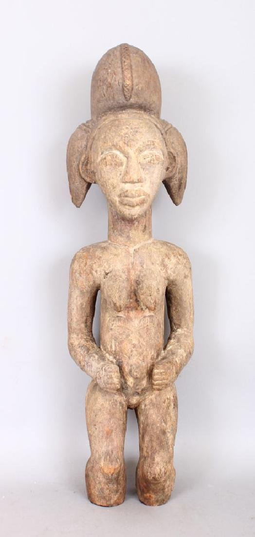 AN EARLY CARVED WOOD TRIBAL FIGURE with lime pigment.