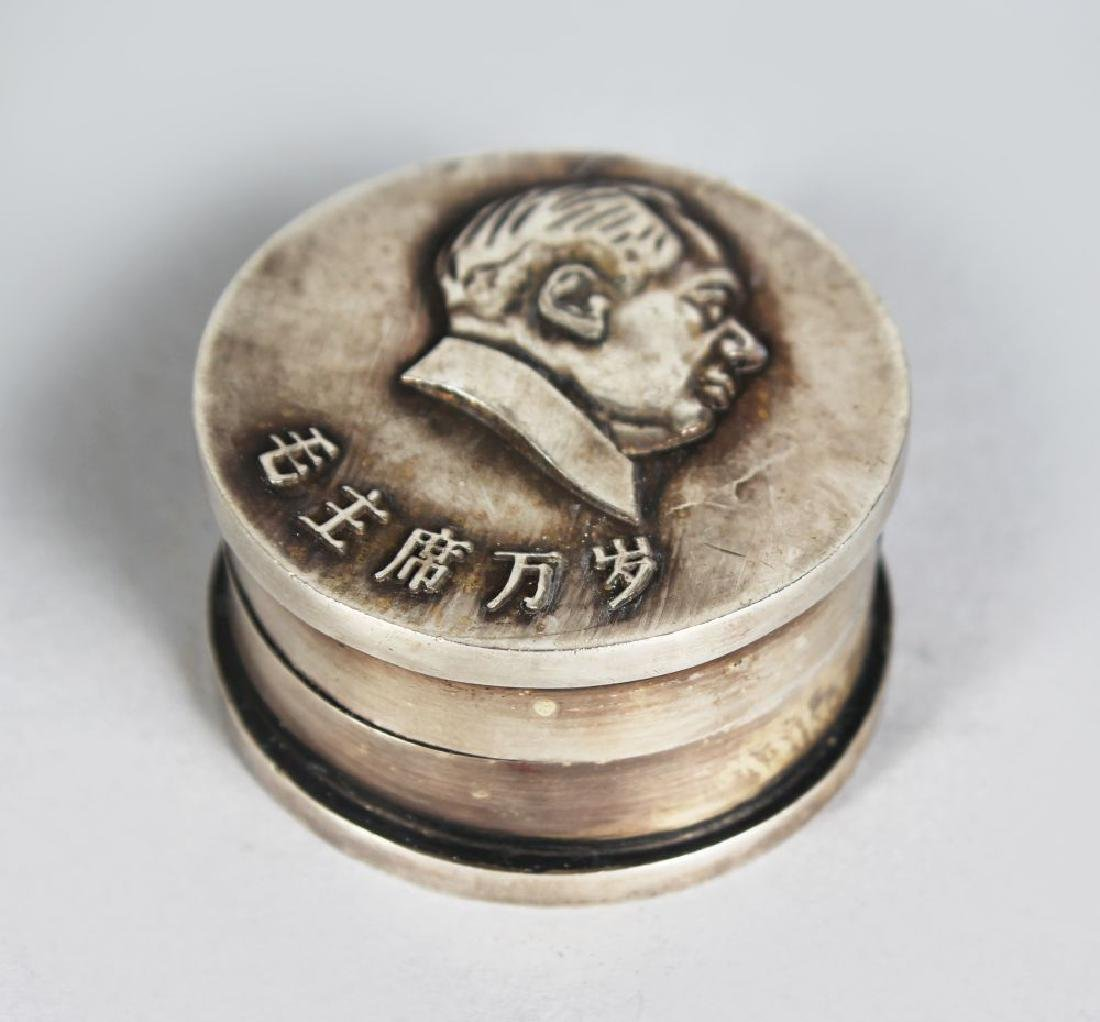 A CHINESE SILVER COIN BOX.  1.5ins diameter.