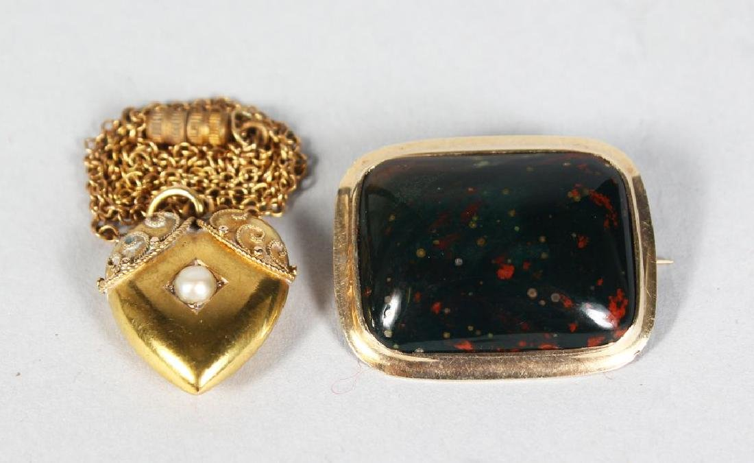 A SMALL GOLD LOCKET AND CHAIN, and a small gold brooch