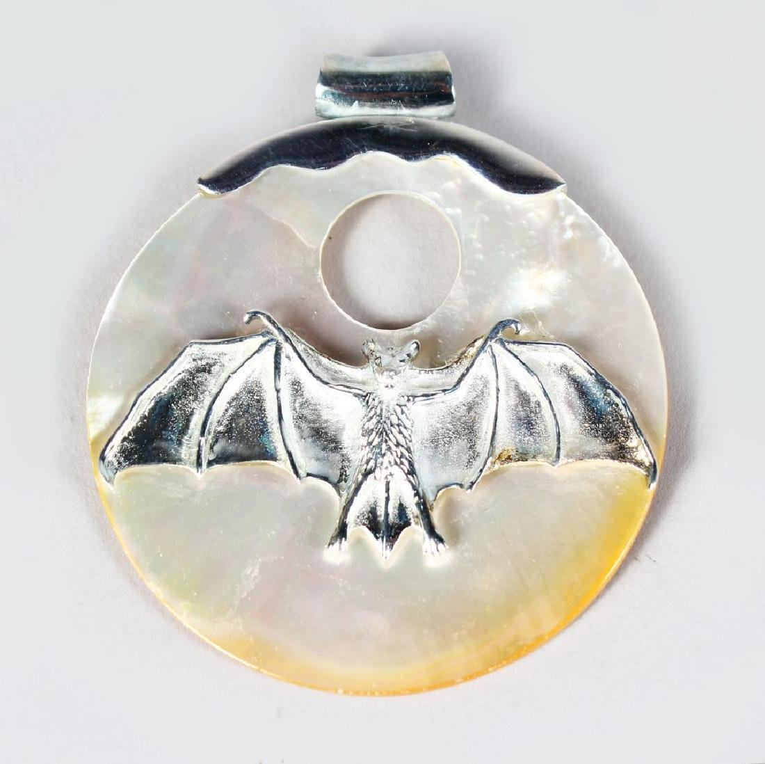 A silver and mother-of-pearl bat pendant.