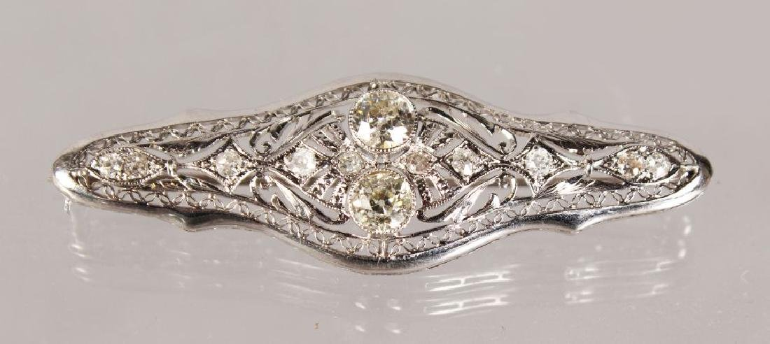 AN ART DECO WHITE GOLD BROOCH with two diamonds and