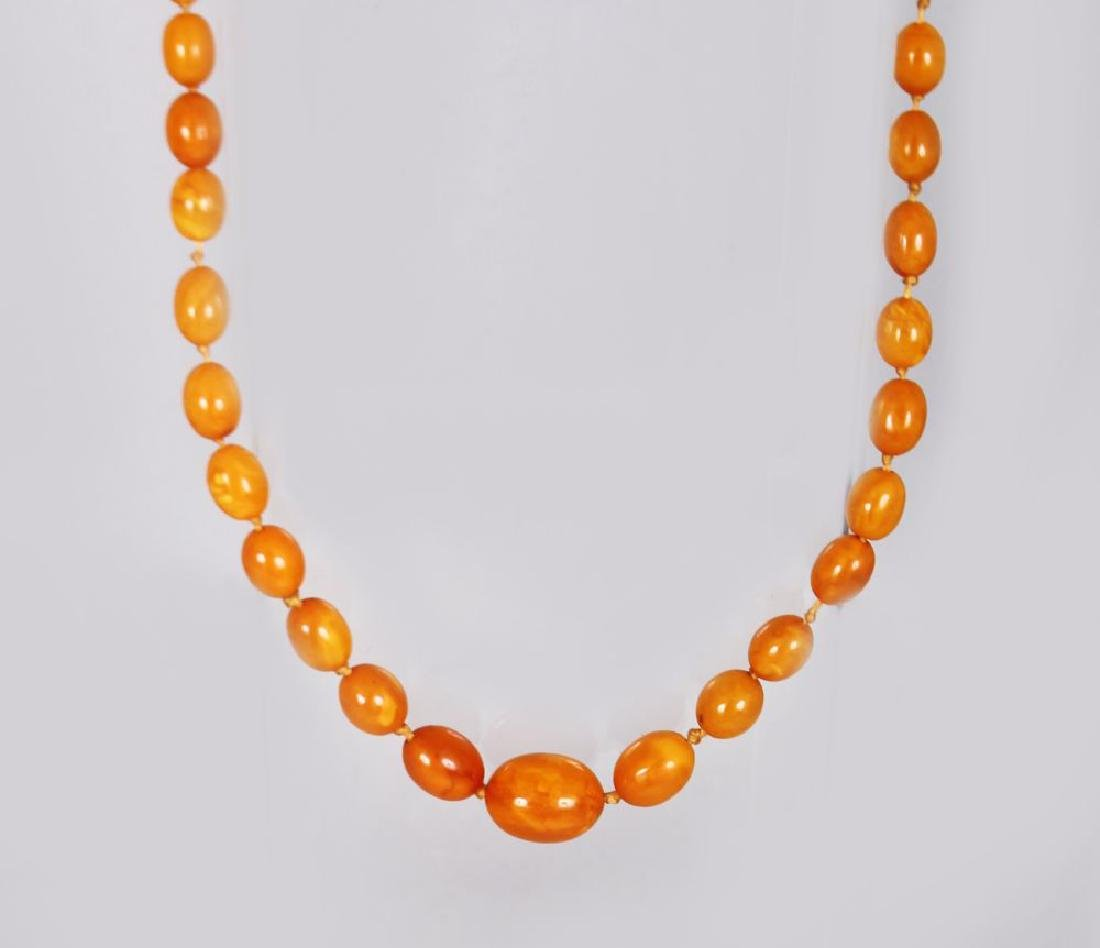 A STRING OF THIRTY-TWO BUTTERSCOTCH AMBER BEADS, 20gms.