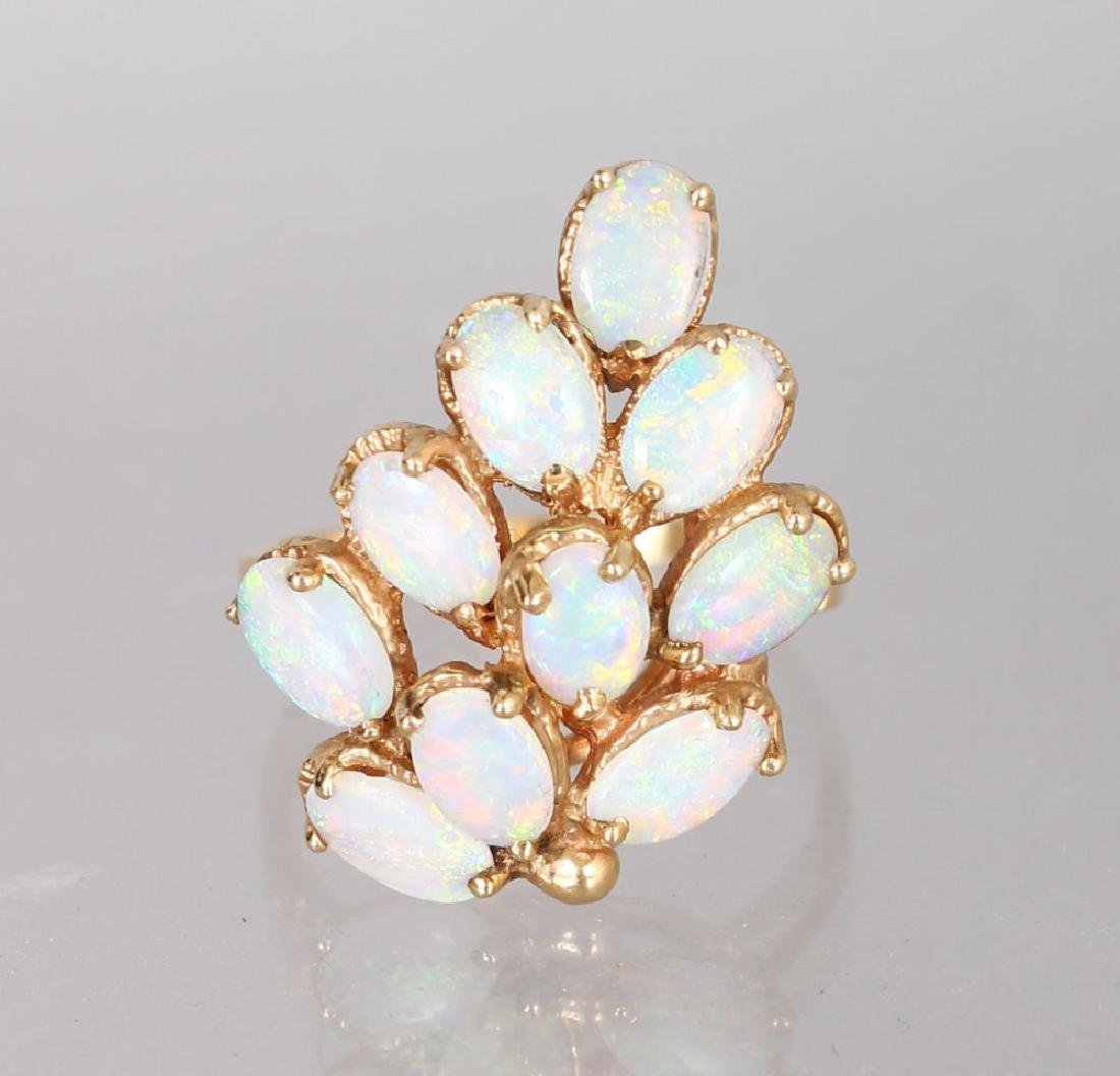 A YELLOW GOLD AND OPAL CLUSTER RING.
