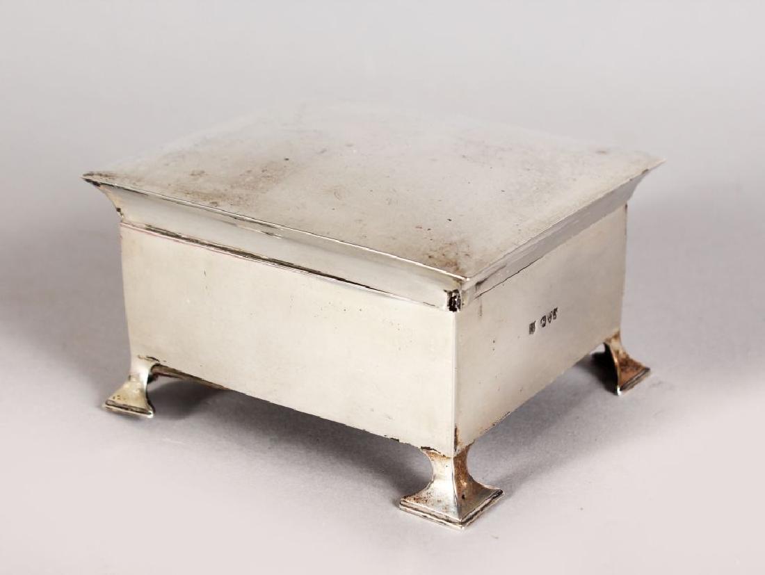 AN ART DECO SILVER CIGARETTE CASE, on bracket feet,