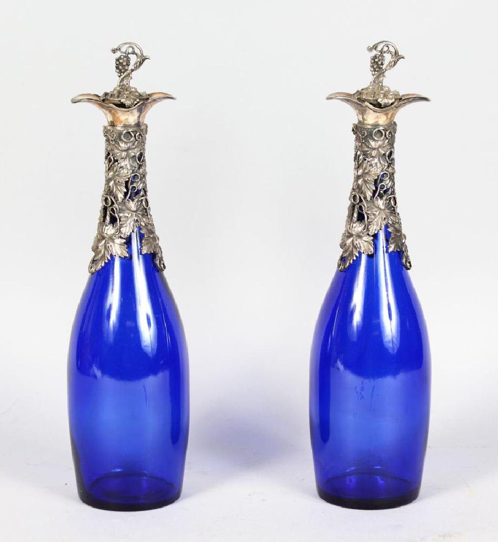 A PAIR OF BRISTOL BLUE BOTTLES, with plated cast mounts