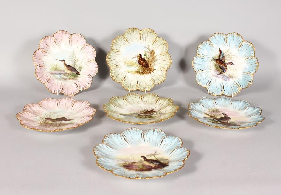 A SET OF SEVEN LIMOGES PLATES, painted with birds.