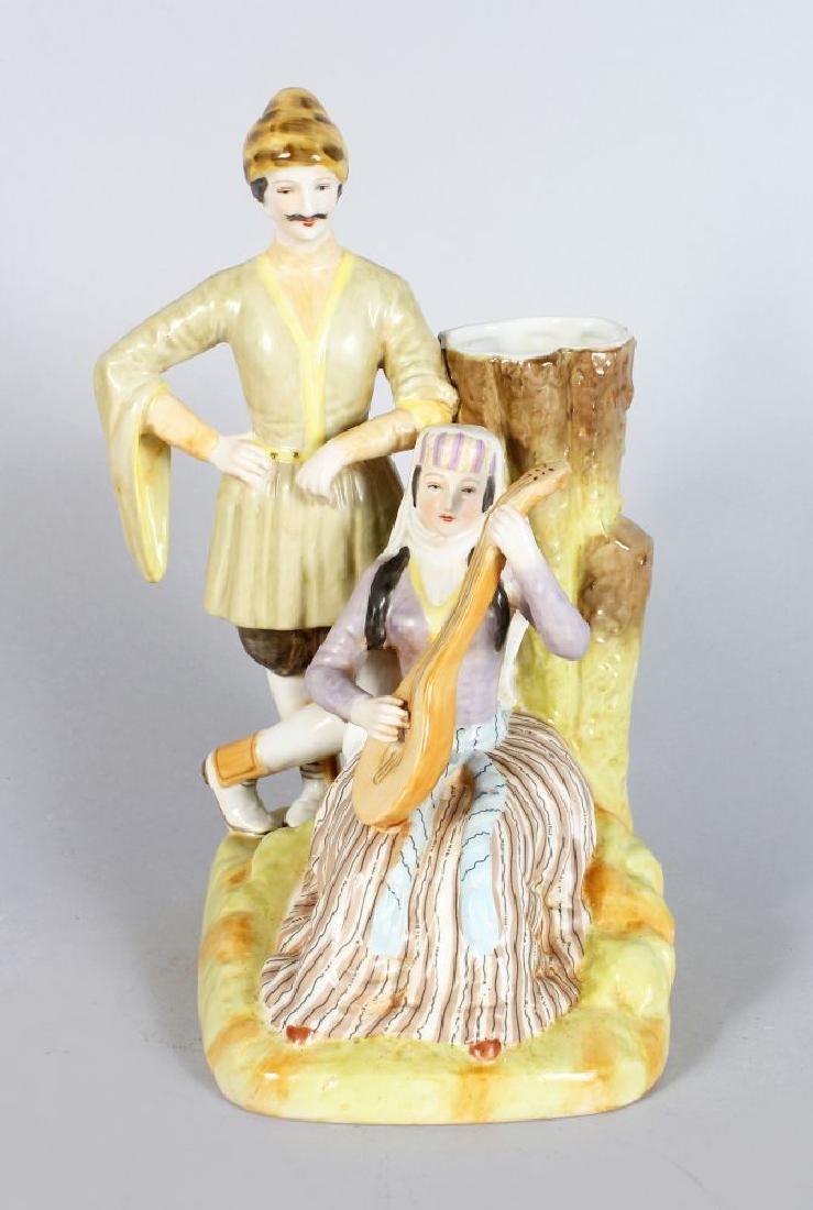 A PORCELAIN SPILL VASE MODELLED AS RUSSIAN LOVERS. 9ins
