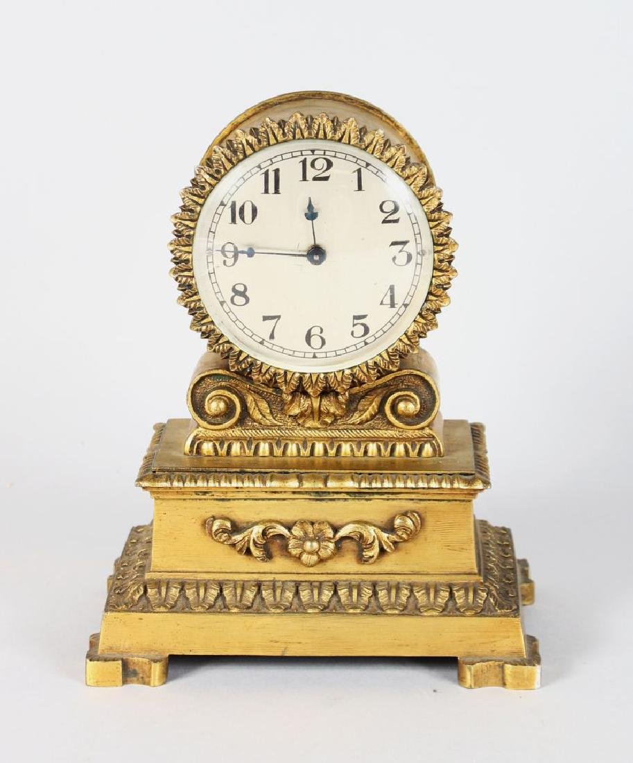 A SMALL EMPIRE GILT METAL CLOCK.  7ins high.