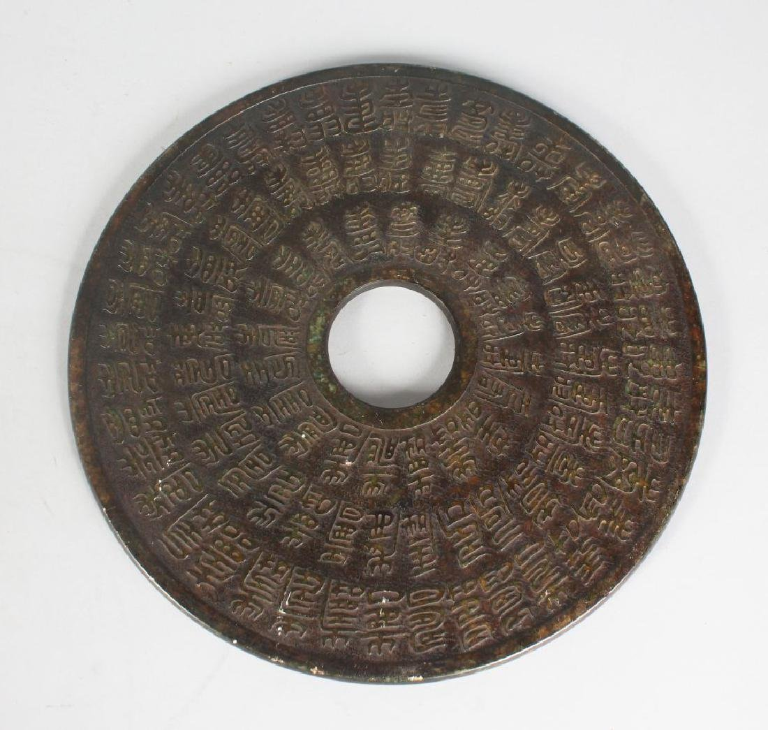 A LARGE CHINESE DISC, carved with calligraphy.  12ins