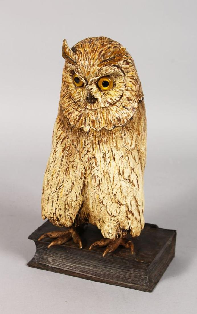 AN AUSTRIAN COLD PAINTED OWL standing on a book.  10ins