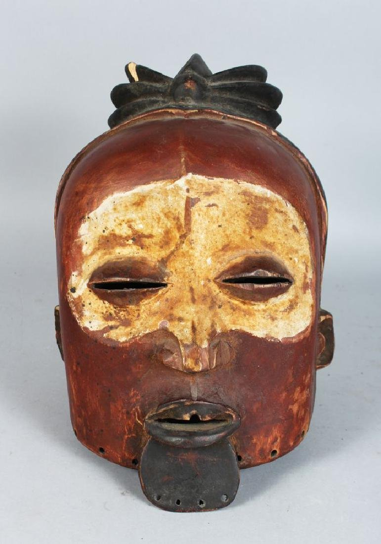 AN ASIAN POLYCHROME CARVED WOODEN HELMET MASK,  finely
