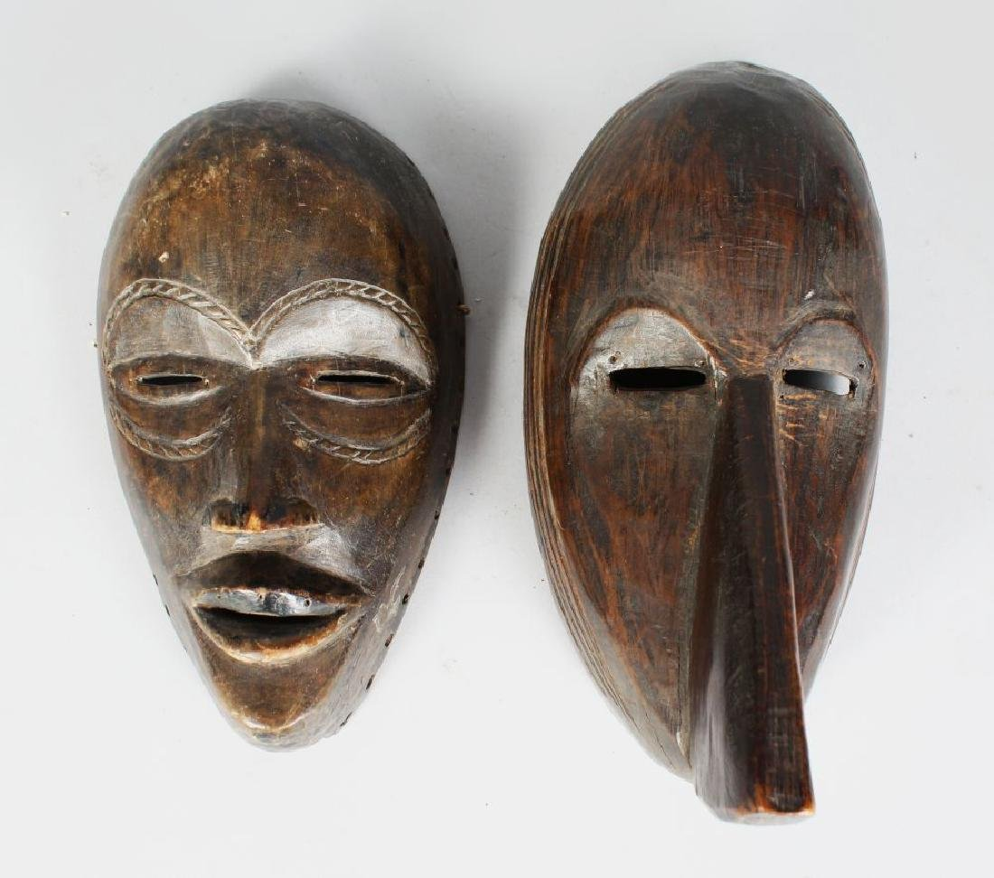 TWO AFRICAN CARVED WOOD MASKS, with pierced eyes, with