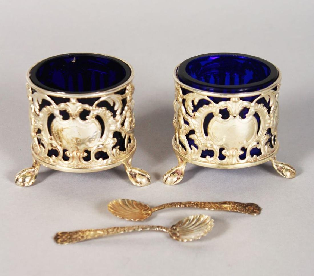 A PAIR OF PIERCED SILVER SALTS with sapphire blue
